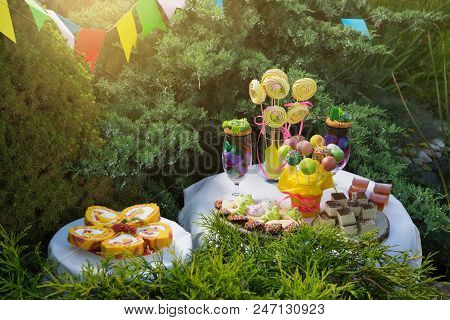 candy bar for birthday, a large assortment of sweets, cakes, candies, a pop and cake pops and other sweets at two dessert tables, an outdoor party poster