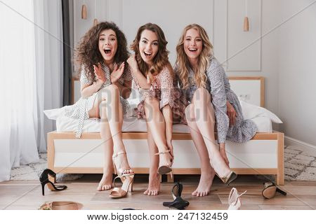 Image of pretty stylish women 20s wearing dresses trying on summer stilettos or high heels during bridal shower in posh apartment