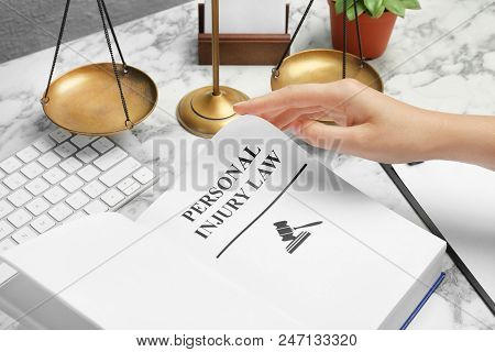 Woman Turning Page Of Book With Words Personal Injury Law At Table, Closeup