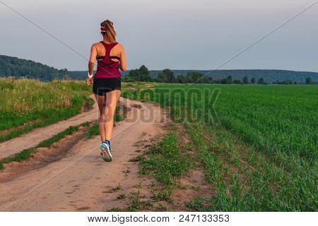 Athletic Blonde Teenage Girl Running At Dirt Road In Field. Sport Girl Running Outdoor. Young Woman