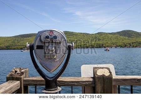 A Binocular Viewer Stares Out At The Beautiful Scenery At Lake George