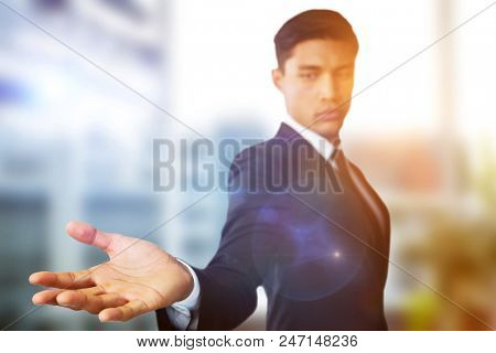 Confident businessman showing hand against white background against laptop on desk by glass window in office
