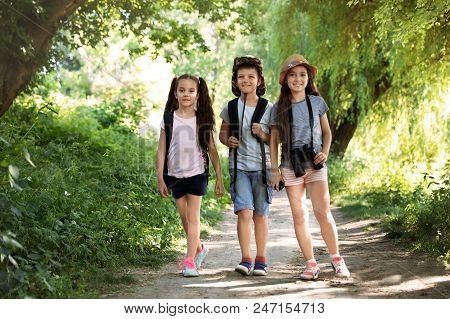 Little Children With Backpacks On Path In Wilderness. Summer Camp