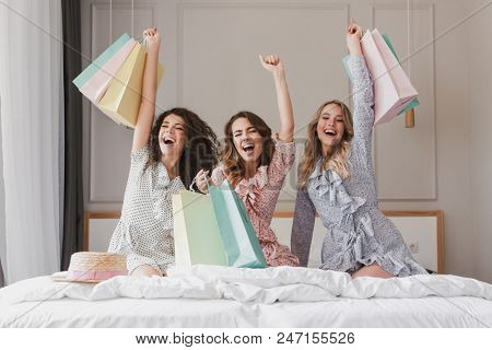 Happy photo of lovely smiling women 20s wearing dresses rejoicing and screaming with colorful shopping bags in hands while sitting on cozy bed in hotel room during hen party poster