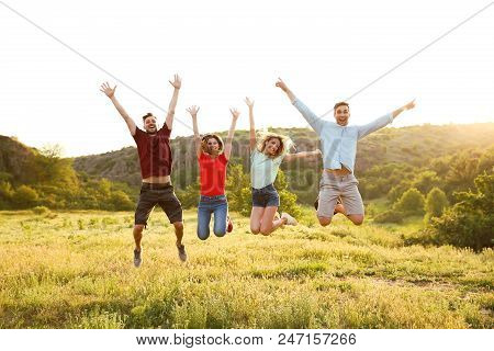 Happy Young People Jumping In Wilderness. Camping Season