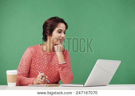 Pretty Indian University Student Reading Information On Laptop Screen And Taking Notes