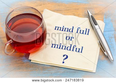 Mind full or mindful   Inspiraitonal handwriting on a napkin with a cup of tea.