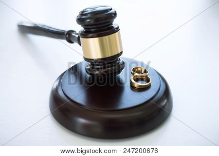 Close Up Of Judge Gavel Deciding On Marriage Divorce And Two Golden Marriage Ring.