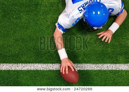 Foto aérea de um jogador de futebol americano fazendo um touchdown de uma mão. O uniforme que ele é drinkin
