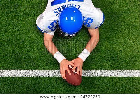 Obenliegende Foto eines American-Football-Spielers machen einen Touchdown mit beiden Händen am ball. Die Vereinten Nationen