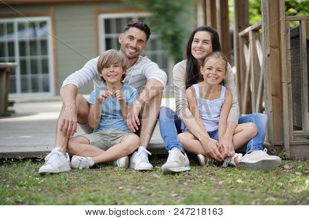 Happy family of four sitting in yard