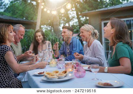 Friends enjoying summer barbecue dinner in garden