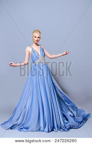 Full length portrait of a magnificent young woman in elegant long blue dress with lush skirt.