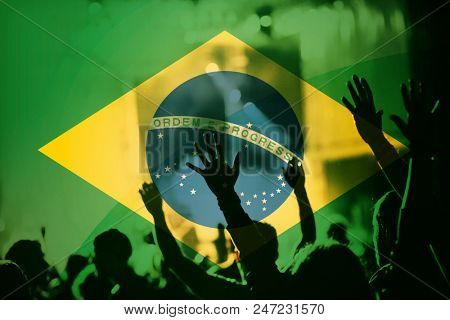 soccer fans supporting Brazil - double exposure of crowd in stadium with raised hands against Brazil flag