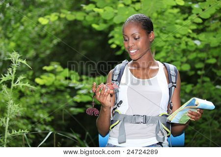 Woman stood outdoors holding compass and map