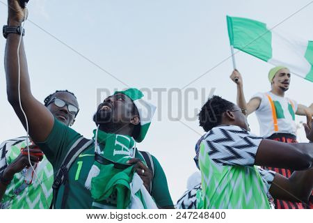 ST. PETERSBURG, RUSSIA - JUNE 26, 2018: Nigerian football fans with national flag at Saint Petersburg stadium before the match of FIFA World Cup 2018 Nigeria vs Argentina. Argentina won 2-1