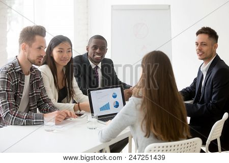 Excited Diverse Work Team Employees Listening Attentively To Female Group Leader Talking, Explaining