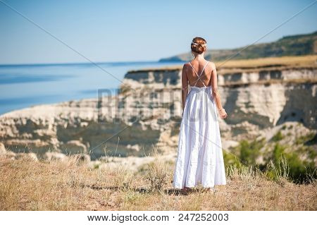 A Girl In A White Sarafan Stands And Takes Pictures Of The Beautiful Nature Of Rocks And Water. Clif