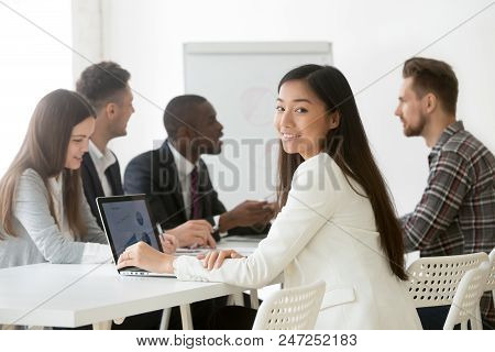 Portrait Of Smiling Asian Company Worker Looking At Camera, Working At Laptop During Business Briefi