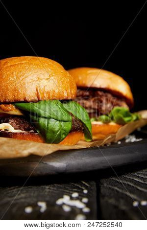 Tempting fast food diner with hot delicious burgers on wooden board poster