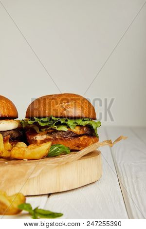 Close-up view of tempting fast food diner with hamburgers and potatoes poster