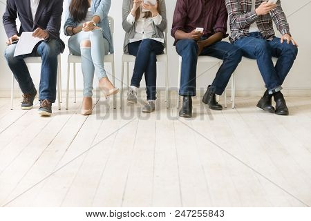 Close Up View Of Diverse Work Applicants Sitting Together, Holding Smartphones, Tablets And Papers G