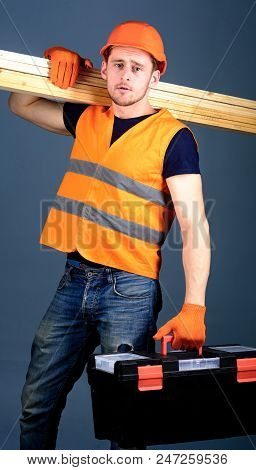 Man In Helmet, Hard Hat Holds Toolbox And Wooden Beams, Grey Background. Carpenter, Woodworker, Labo