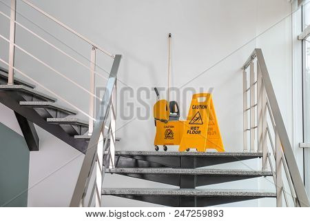 Safety Sign With Phrase Caution Wet Floor And Mop Bucket On Stairs. Cleaning Service