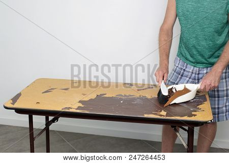 Male Cleans Off Table He Is Preparing To Resurface Male Sweeping Off A Table With A Dustpan And Broo