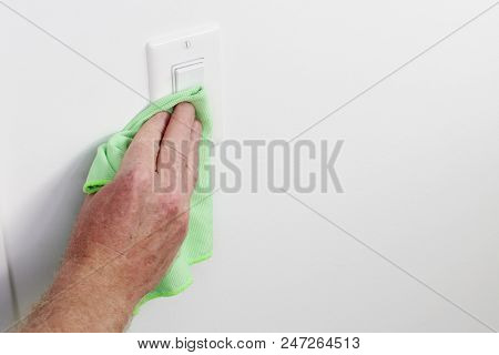 White Panel Light Control Cleaning By Hand Cloth. Male Hand Dusting Light Switch With Cleaning Cloth
