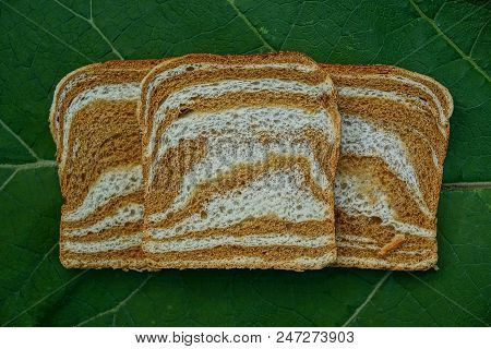 Three Pieces Of Square Colored Bread On A Green Leaf