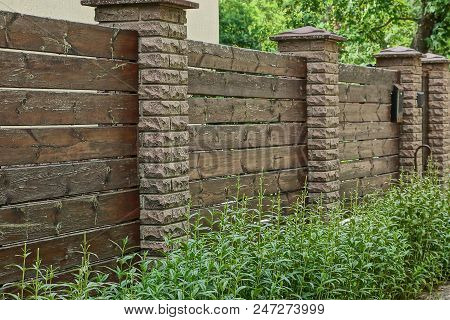 Part Of A Brown Fence Of Wooden Boards And Bricks In Green Grass