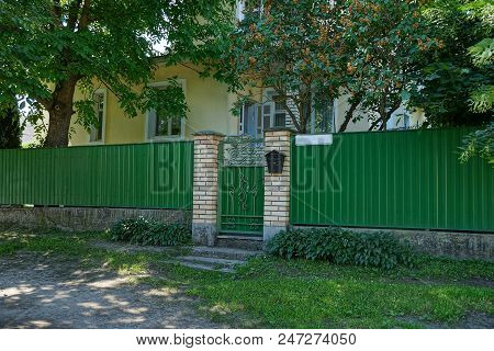 A Green Metal Fence And A Closed Door On The Street Near The Road
