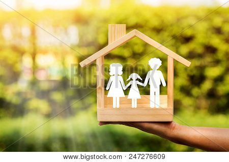 Woman Hand Holding A Wooden Home With Happy Family Of Paper Art Is Placed Inside On Nature Bokeh In