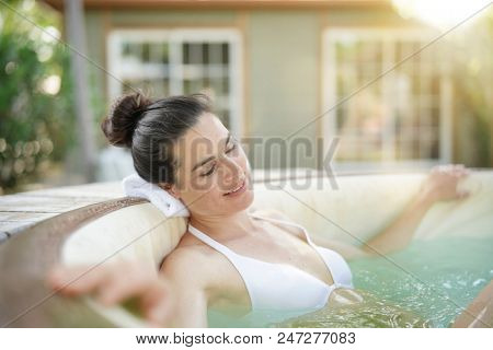 Attractive brunette woman relaxing in spa hot water