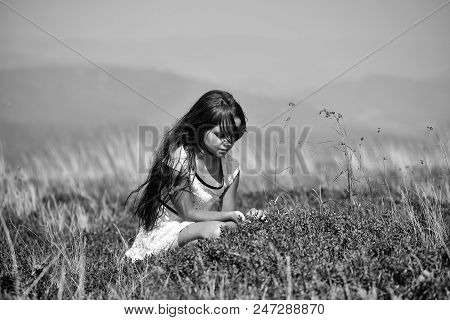 Happy Kid Having Fun. Little Pretty Brunette Girl In White Lace Summer Dress Sitting In Mountain Val