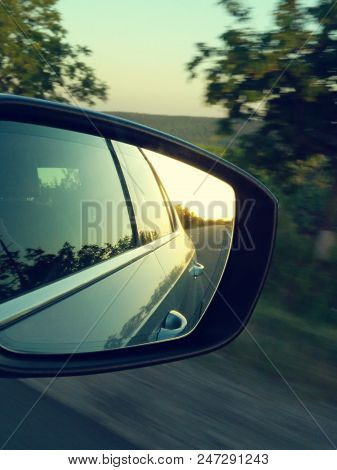 Reflection Of Sunny Road At The Car Side Mirrow. Rear View Mirror Reflection On Sun Down.