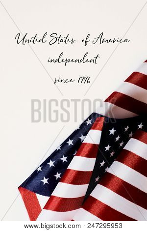 some american flags and the text united states of america independent since 1776 against an off-white background