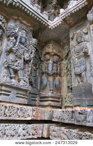 Ornate bas relieif and sculptures of Hindu deities, Kedareshwara Temple, Halebid, Karnataka, India. poster