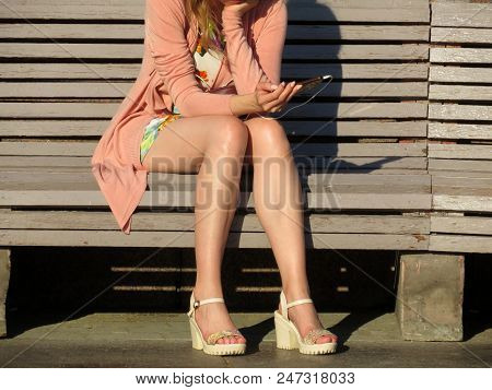 Woman In A Beige Summer Shoes With High Heels Sitting With A Smartphone In Her Hand On The Wooden Be