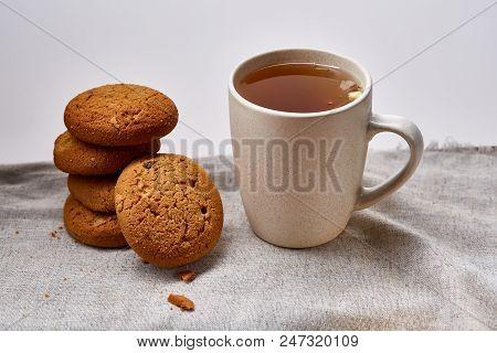 White Porcelain Mug Of Black Tea Or Earl Grey And Pile Of Sweet Cookies On Homespun Napkin Over Whit