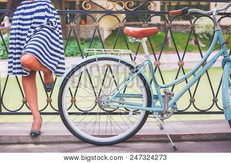Vintage Image Of Young Hipster Girl Standing Near Fence Near Vintage City Bike At The Park. Freedom