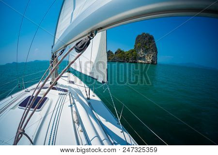 Sailing boat moves under the sails in a tropical sea and aproaches the island