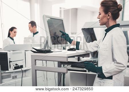 Attention. Waist Up Of Concentrated Skilled Laboratory Assistant Using Computer And Pointing At Scre