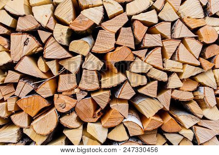 Cut Wooden Logs Texture. Wooden Background. Pieces Of Wood In The Rural Area. Pile Of Cut Wood In Th