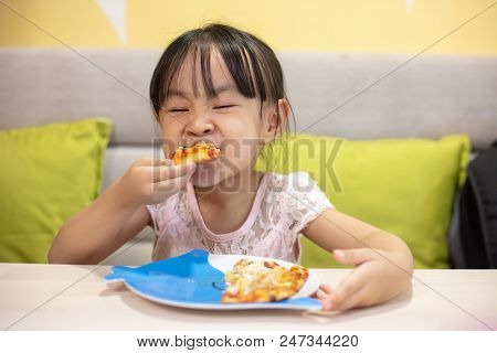 Asian Little Chinese Girl Eating pizza at restaurant poster