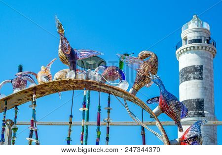 Murano, Italy - April 25, 2008:  A Typical Glass Works With The Lighthouse In The Background