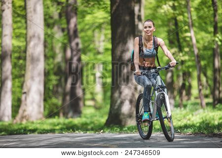 Full Length Portrait Of Vigorous Lady Is Backpacking In Marvelous Nature On Bicycle. She Is Slowly P