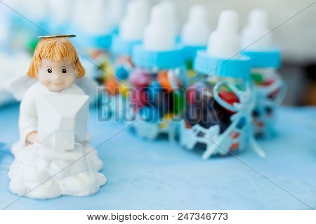 Candy bar on baby's christening party for boy with a lot of different candies. Decorated in blue colors with angel poster