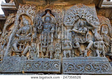 Ornate wall panel reliefs depicting from left Deity playing damaru, Vishnu and dancing Sarswati, Hoysaleshwara temple, Halebidu, Karnataka, India. poster